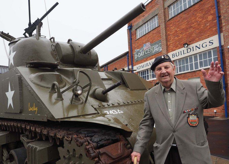 Normandy veteran Richard Phillips standing by a Sherman tank