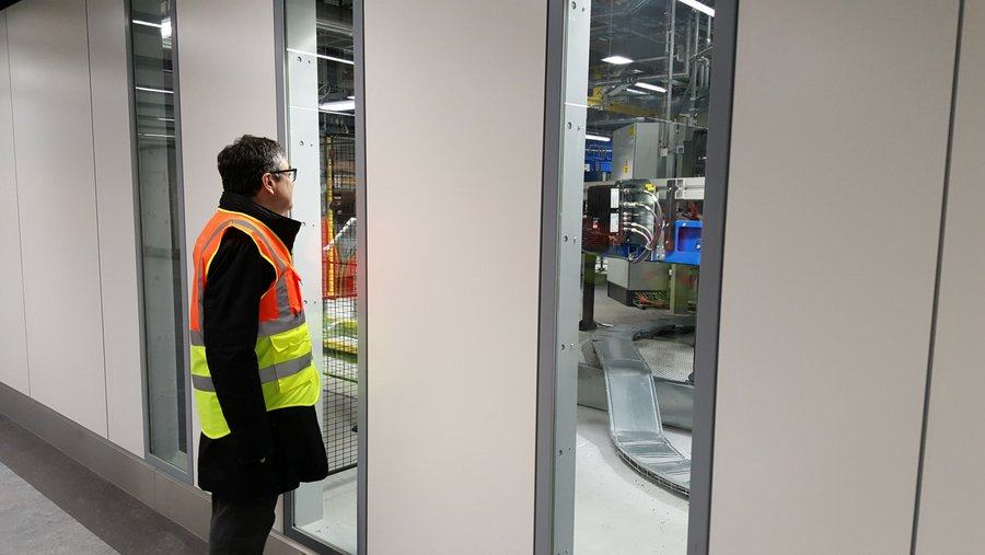 Man looking through window at automated baggage system