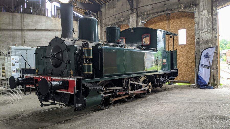 Shiny green steam engine inside the roundhouse