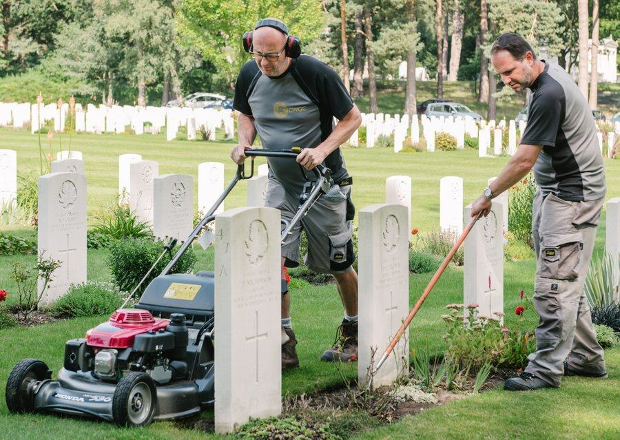 One CWGC gardener pushes a lawnmower past a row of headstones in a cemetery while another tends the flowers