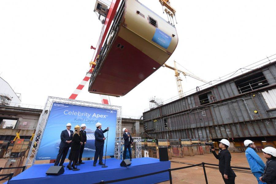 Directors & VIPs in white hard harts on a stage awaiting the first block of the new ship as it is lowered by a crane behind them