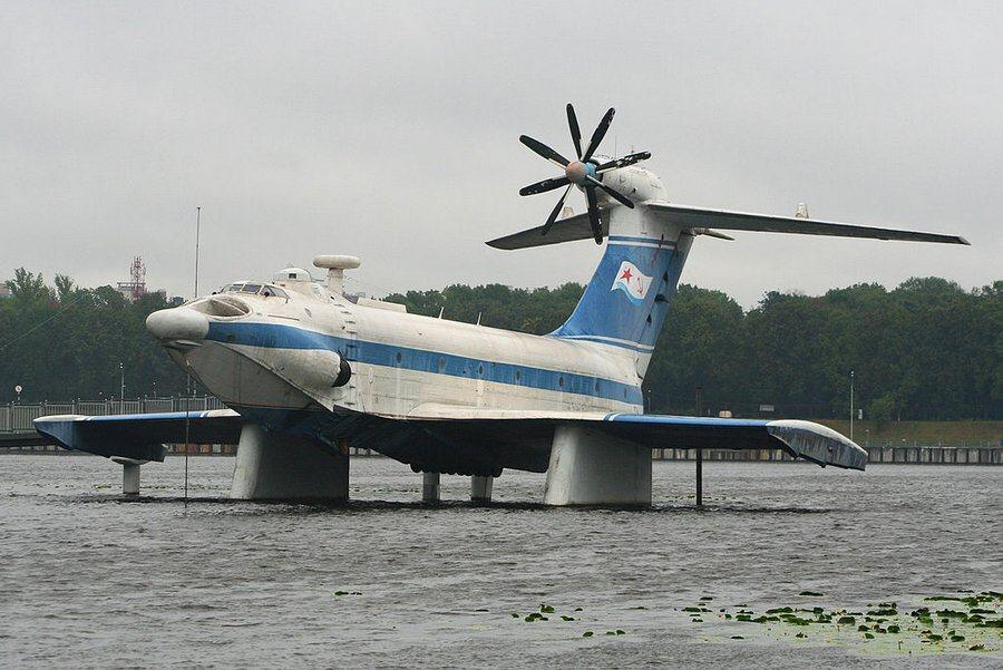 A large blue & white passenger carrying ekranoplan displayed on pylons over the water in a Moscow park