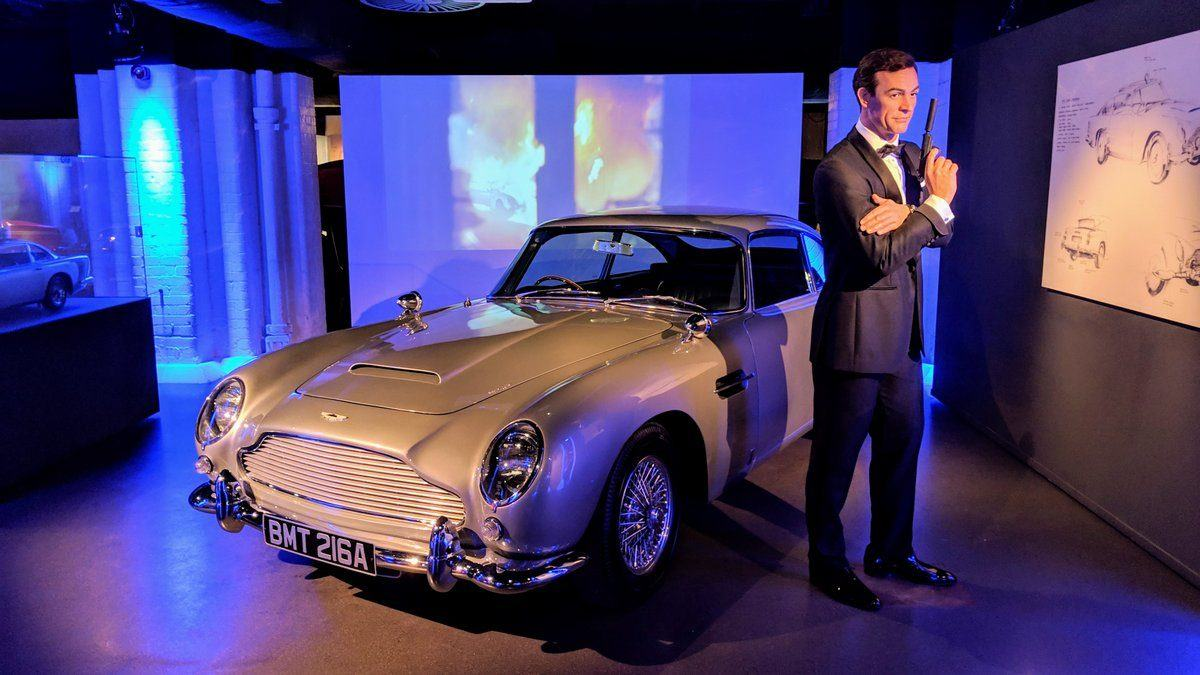 A not-very-lifelike dummy of James Bond in dinner jacket and with a gun, stands next to his silver grey Aston Martin DB5