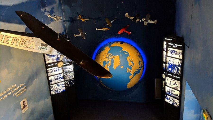 A dark room with a large Earth globe surrounded by suspended model aeroplanes