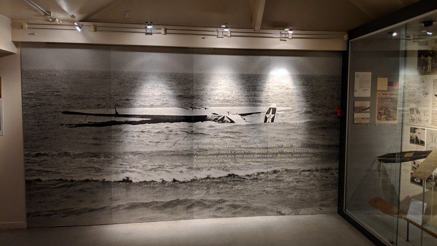 Wall-sized B/W photo of the ditched 'America' in the sea
