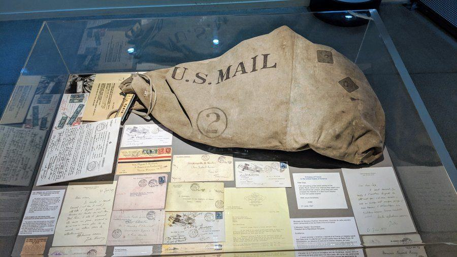 Mail sack in a display case with letters arranged around it