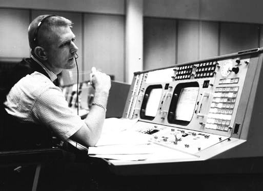 Black & white photo of Gene Kranz at a control room console