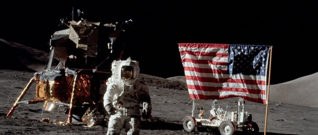 Astronaut stands on the moon in front of their landing capsule, moon buggy, and an American flag