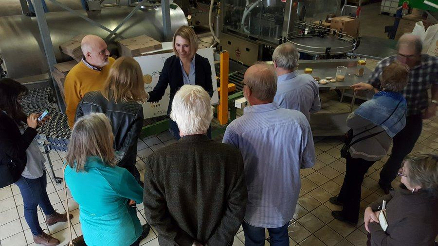 A factory tour group stand listening to a young woman explaining the workings of a micro-brewery