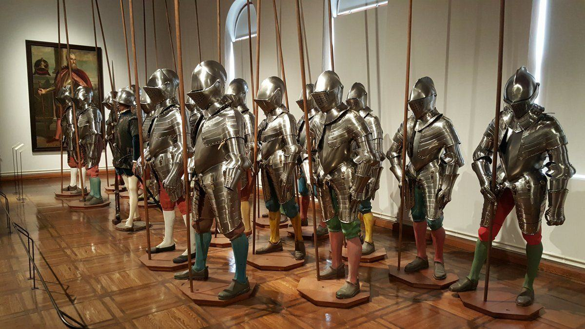 19 mannequins standing together wearing shiny foot soldiers armour and coloured leggings, holding pikes