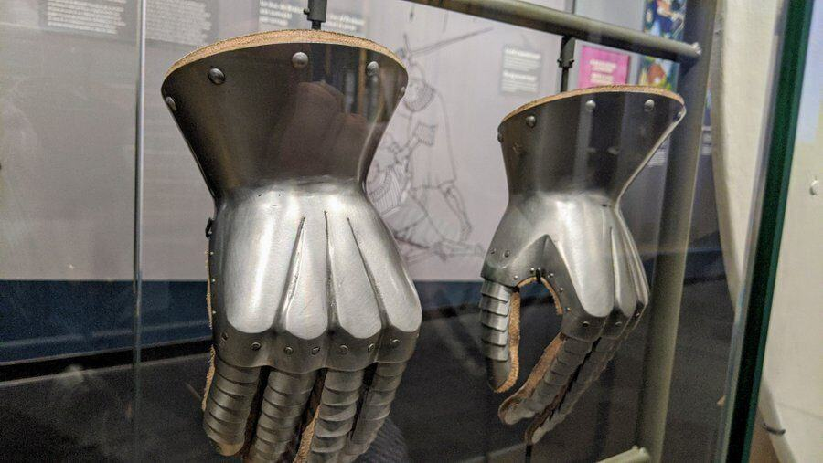 A pair of armoured gloves - a fabric palm with steel on the outside