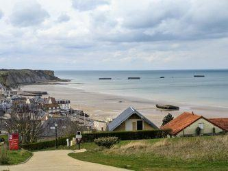 View looking down on the town of Arromanches, its beach, and Phoenix caissons out to sea