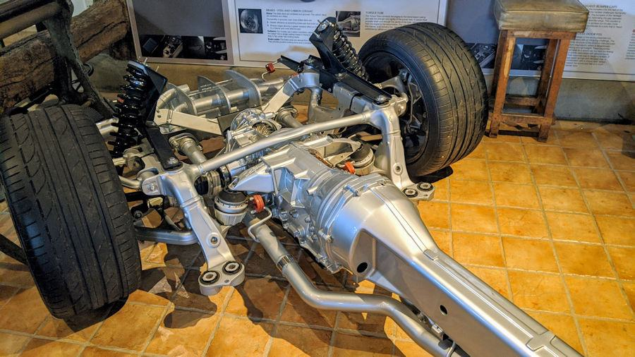 A silver engine and chassis on wheels for the Aston Martin Rapide