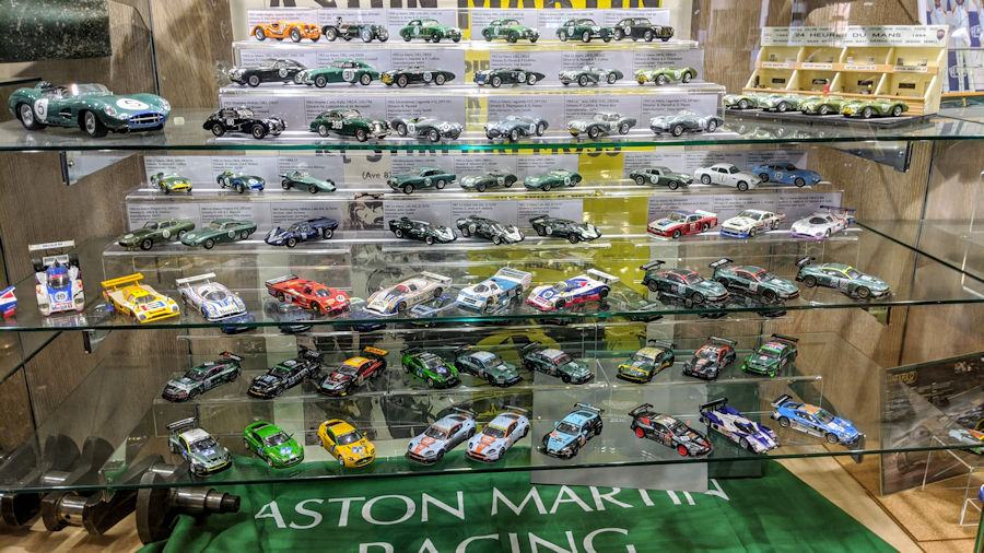 A glass cabinet with shelves full of model racing cars at the Aston martin Museum