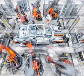 Fast moving orange robot arms work on a car chassis in the Audi factory