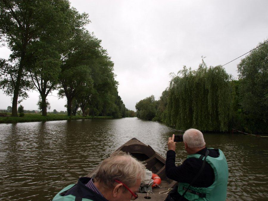 Looking forward down a canal with fellow passengers in the bow of the boat wearing green lifejackets and taking photos