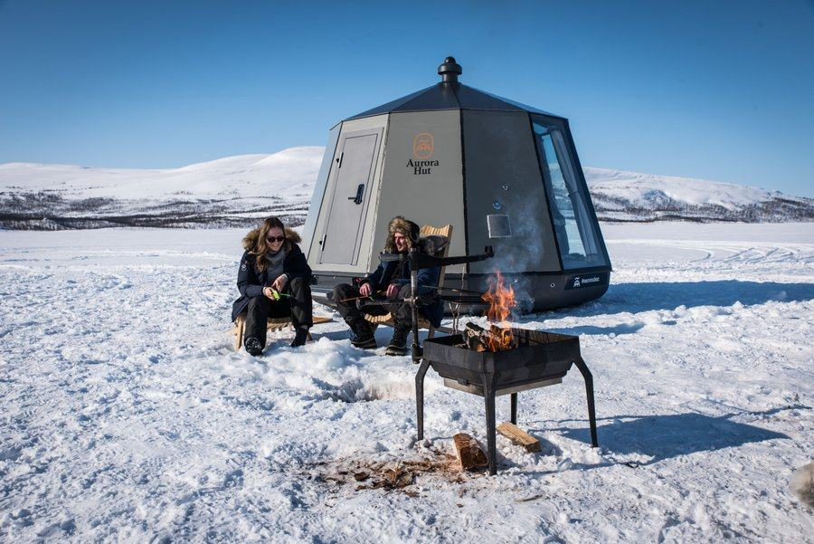Two people sit by a BBQ outside a pod in a show field