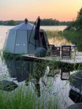 A floating igloo with a deck on a lake at sunset