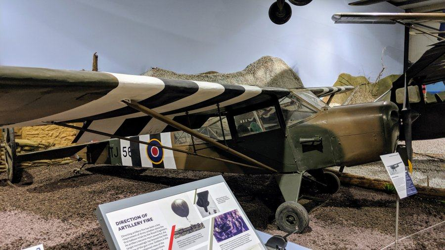 Small single-propeller light aircraft with D-Day B/W invasion stripes painted on the wingson