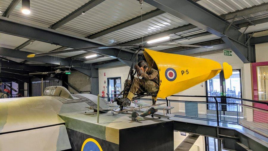 A soldier sits in a metal frame with rotors above and a small yellow fuselage