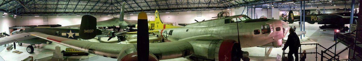 A panorama view of the, fairly dark, hanger with a silver four-engined  B-17 Flying Fortress with a yellow tail and red painted engine nacelles in the foreground