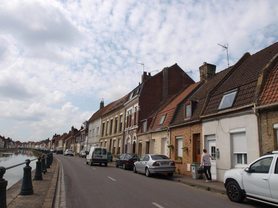 Canalside street in St Omer with a row of houses