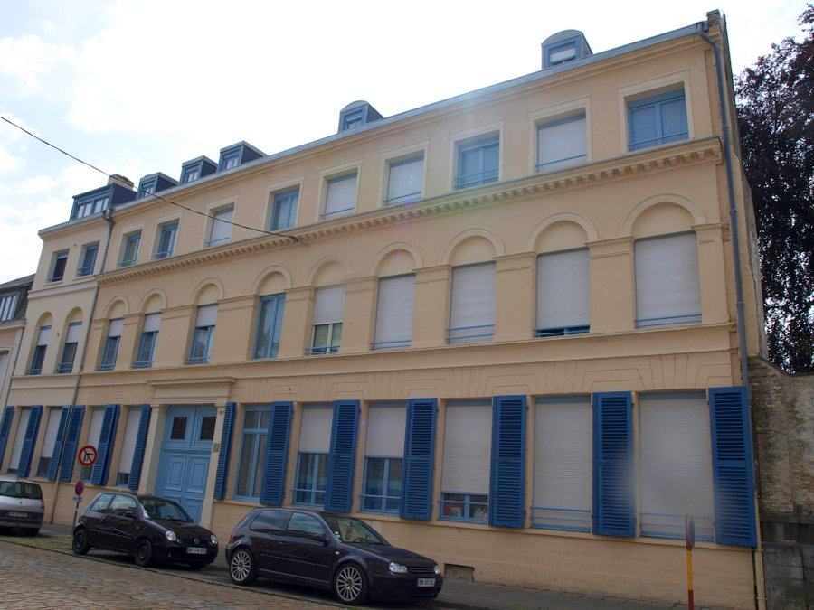 A cream coloured 3-storey building with blue shutters in St Omer