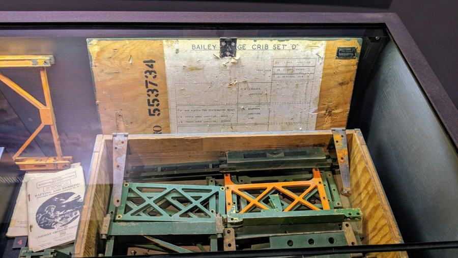 A wooden box with model components of a girder bridge