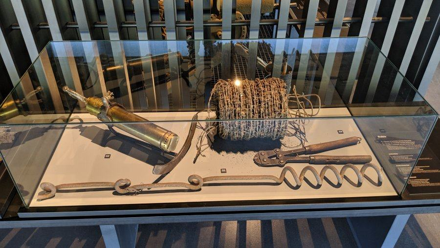 A display case with a role of barbed wire, cutters, and stakes