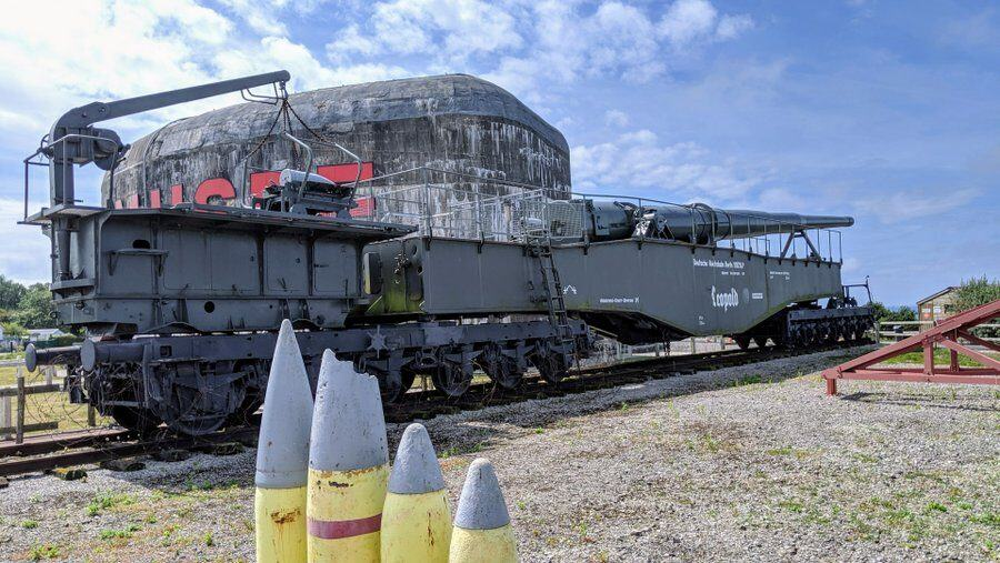 Some yellow artillery shells in the foreground with the railway gun behind
