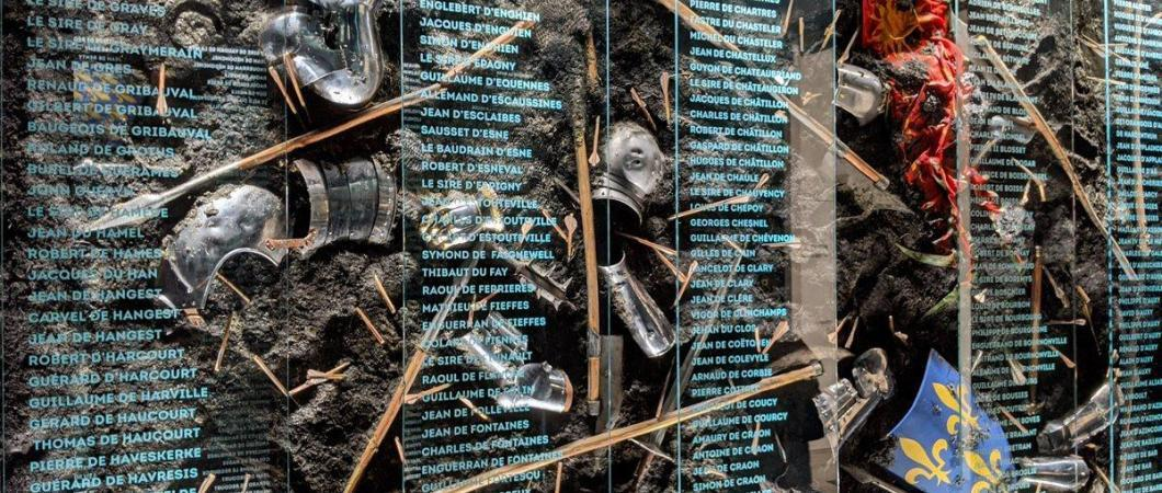 A wall display of broken armour, weapons & flags in mud with an overlay of names in white print