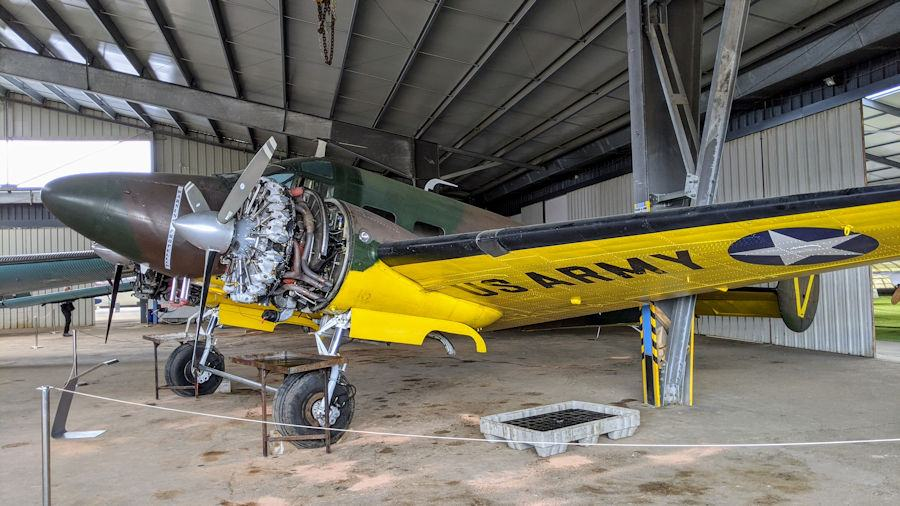 Twin-engined - one of them undergoing maintenance - WW2 transport aircraft in brown & green camouflage and yellow undersides to the wings. The Beech 18 is on display at the Salis Flying Museum