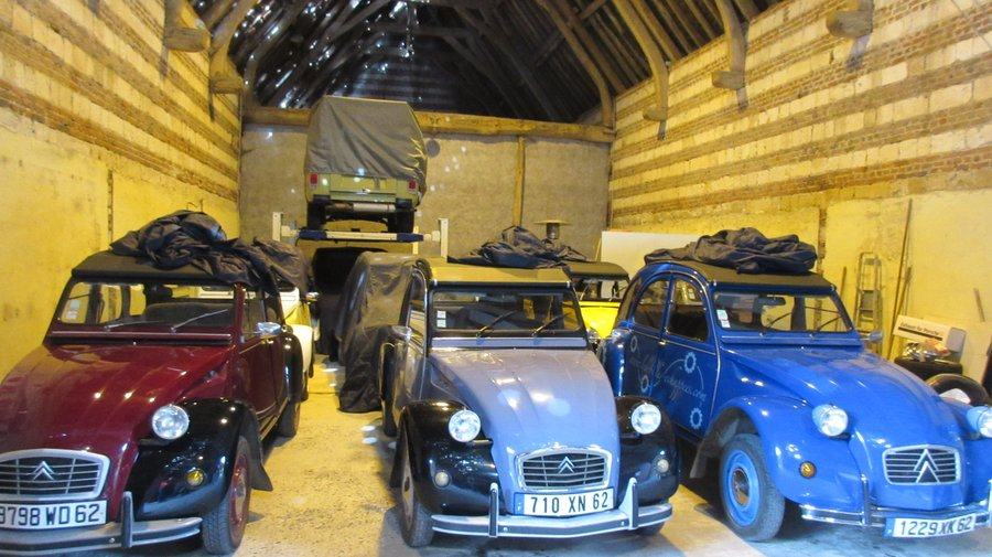 A barn full of classic cars, mostly Citroen 2CVs