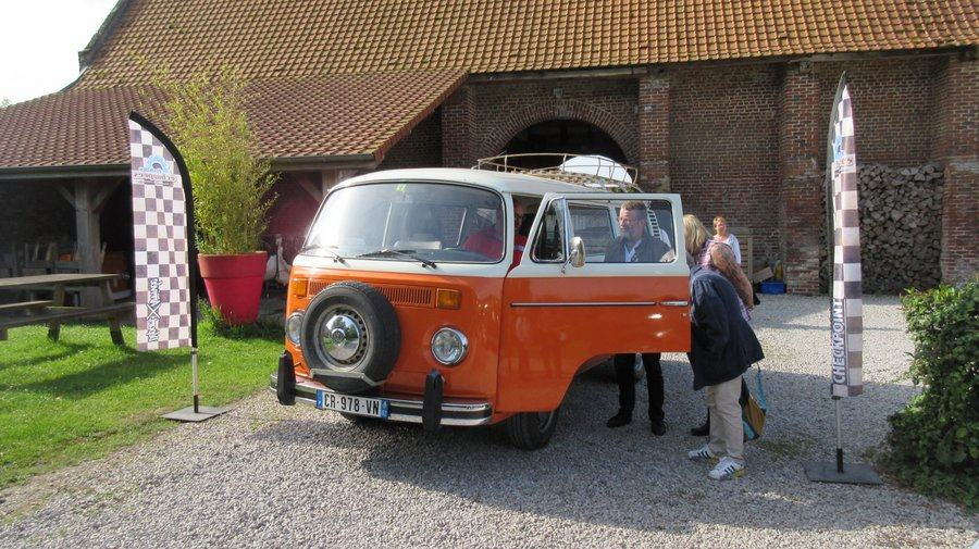 A family are getting ready to board their orange coloured VW combi van