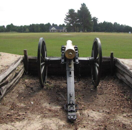 Cannon in an earthwork entrenchment at Bentonville, looking across a green field