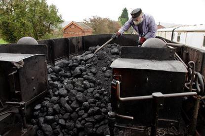 A fireman rakes coal in an open tender