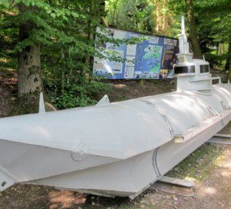 A small grey submarine on a woodland path