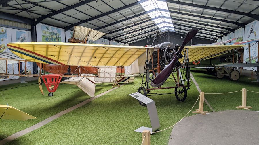 Early monoplane with lots of wires supporting the wings from underneath and above. The Bleriot X1 is on display in a hanger at the Salis Flying Museum