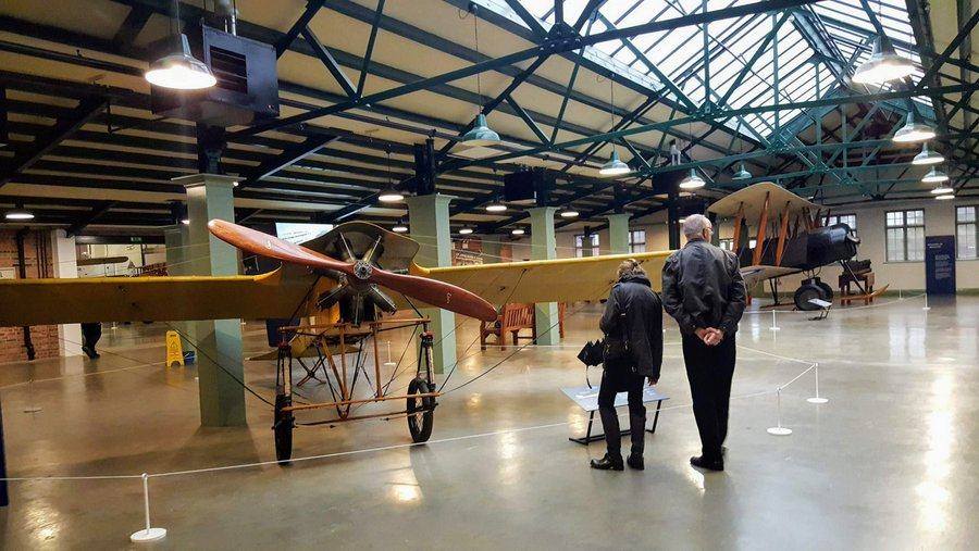 Two visitors look at the sign under the yellow bleriot monoplane. The green Avro 504 biplane in in the background.