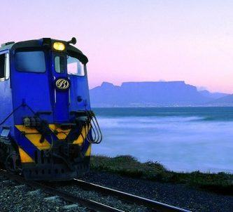 Blue painted diesel loco pulling the luxury coaches on a piece of track by the mauve coloured sea at sunset