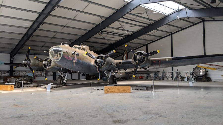 Large, brown painted, four-engined WW2 B-17 bomber in a hanger at the Salis Flying Museum
