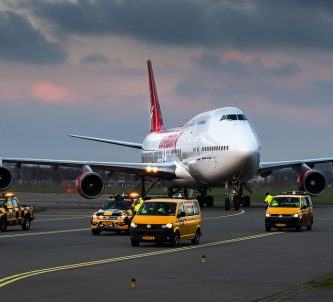 A jumbo jet moving on a taxiway surrounded by yellow vehicles