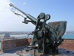 Anti-aircraft gun pointing skyward, a grey sea and blue sky behind