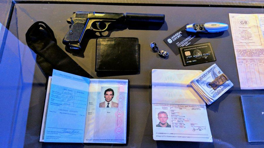 A gun with a silencer, old and new style passports , driving license, a wad of cash and a 'Universal Exports' business card