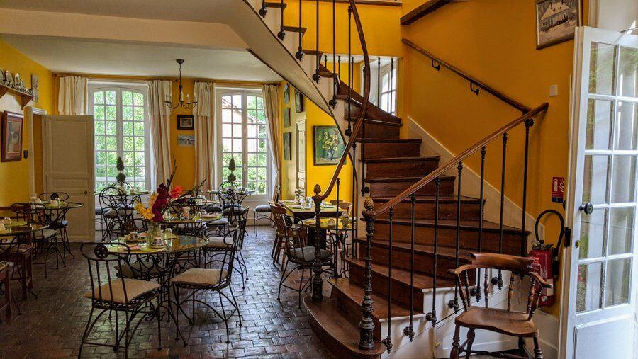 Yellow painted room with tables & chairs and a curved staircase