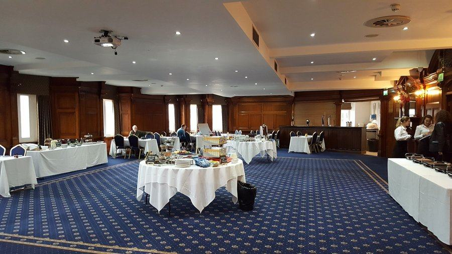 A large, wooden panelled room with rich decorations a deep blue carpet and breakfast tables & guests