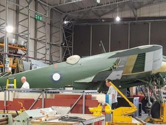 Two men work on a green painted Bristol Beaufighter in a hanger