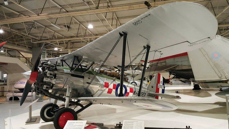 Silver biplane with red & white chequered markings on the side.