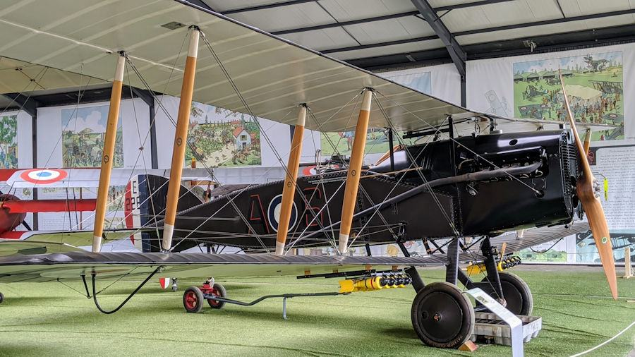 Green-painted WWI British biplane with roundels and a gunner position behind the cockpit, on display at the Salis Museum of Flying
