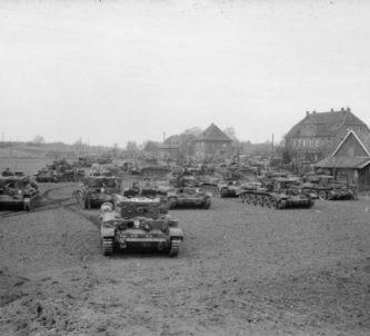Black & white photo. A crowd of tanks on the outskirts of a village